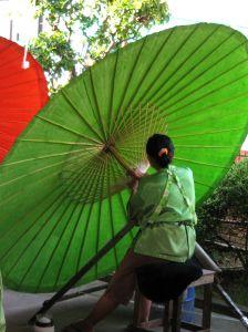 Thailänderin bei der Herstellung eines traditionellen Schirmes